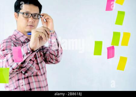 Asian businessmen are sharing their thoughts on the glass wall. Brainstorming concept. Sticky note on glass wall. Dare to express opinions and accept - Stock Photo