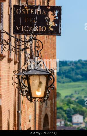 Certaldo, Tuscany / Italy: An ornate street light and a metal sign of Osteria del Vicario in the medieval upper part of town called Certaldo Alto. - Stock Photo