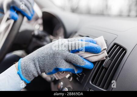 Auto service staff hand cleaning car interior with microfiber cloth. Car detailing and valeting concept