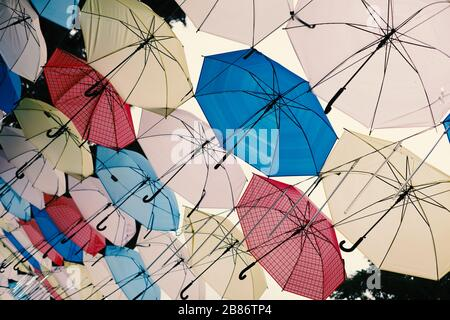 Many multi-colored umbrellas on a background of the cloudy sky. - Stock Photo