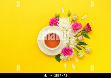 Teacup, a white cup of tea surrounded by pink yellow, green flowers isolated on yellow background. Horizontal image