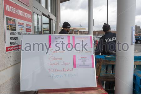 Toronto, Ontario, Canada-March 20, 2020: Board announcing the hygienic products which are out of stock. Policemen watch the store entrance to maintain - Stock Photo