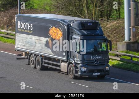 Booths, supermarket food wine & grocery; Haulage delivery trucks, lorry, transportation, truck, cargo carrier, Mercedes Benz vehicle, European commercial transport, industry, M6 at Manchester, UK