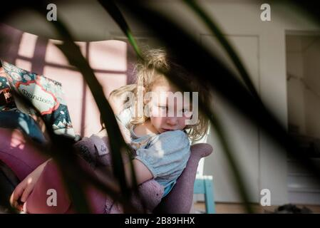 view of a child sitting on a chair at home reading with her brother - Stock Photo