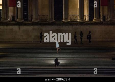 Trafalgar Square, London, UK. 21st March 2020. A woman poses for a photo.Trafalgar Square just after midnight on Saturday. The government advises staying at home and limiting social life. - Stock Photo