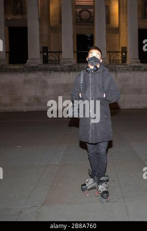 Trafalgar Square, London, UK. 21st March 2020. A skater wear surgical mask due to coronavirus..Trafalgar Square just after midnight on Saturday. The government advises staying at home and limiting social life. - Stock Photo