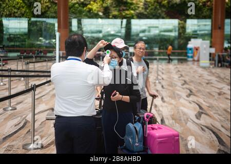 18.03.2020, Singapore, Republic of Singapore, Asia - At Changi Airport an employee takes body temperature readings of passengers to detect a fever. - Stock Photo