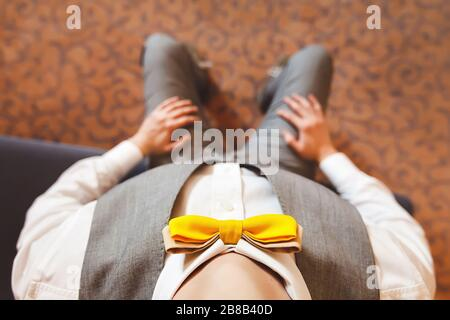 The groom with a yellow butterfly sitting on the bed. The view from the top. The eyes of the groom