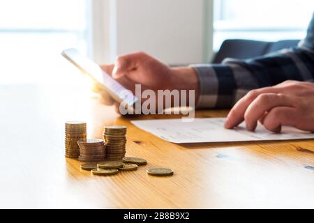 Paying electronic bill with smartphone. Digital internet payment with mobile phone. Man using cellphone and online bank. Reading paper and typing. - Stock Photo