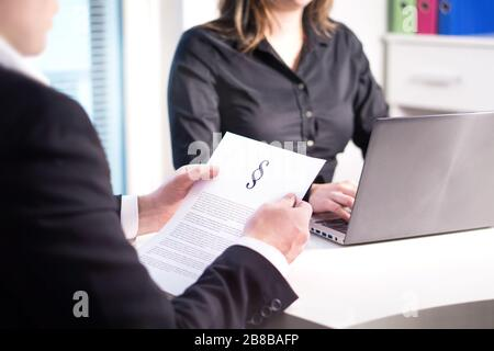 Two lawyers having meeting in office. Professional legal team and company working. Teamwork in law firm. Woman typing with laptop and man reading.