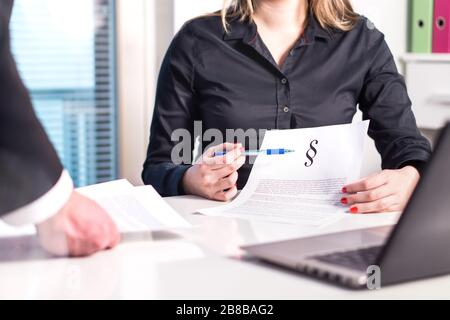 Female lawyer and attorney pointing a legal document in meeting with colleague. Team and company working. Teamwork in law firm.