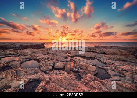 Beautiful colorful sunset near the sea at Cyprus with dramatic clouds and boulders. Reflections in the water. Beauty world natural outdoors travel background