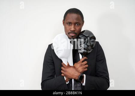 African young man wearing black suit holding white and black plastic masks revealing face - Stock Photo