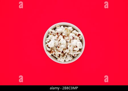 Popcorn in a white bowl on red background. Top view