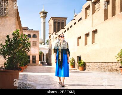 Woman walking in old Dubai, UAE. Traditional Arab street and mosque. Female tourist in historical Al Fahidi neighbourhood wearing dress. Tourism in he - Stock Photo