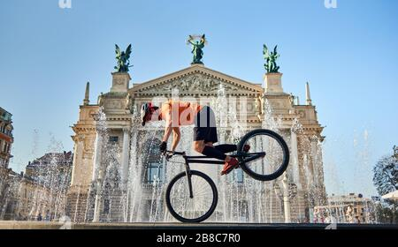 Front view of cyclist standing on front wheel of mountain bike and looking down. Young athlete is cycling downtown near fountain. Concept of active. - Stock Photo