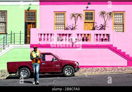 Pastel green next to vivid pink with magenta details. Add a burgundy pickup and a guy in a fluorescent jacket. Brilliant colours on Wale Street. - Stock Photo