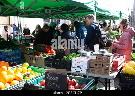London, UK. 21st March 2020.  at Venn Street in Clapham shoppers appreciate fresh fruit and vegetables available at the weekly Saturday market. However, very few wore face masks or observed social distancing advice. Credit: Anna Watson/Alamy Live News - Stock Photo
