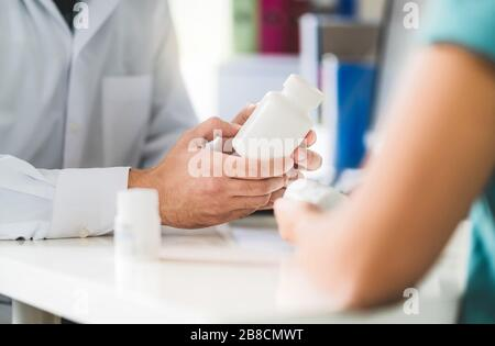 Doctor consulting patient about right medication. Physician holding medicine and pills in hand. Pharmacist in pharmacy in customer service. - Stock Photo
