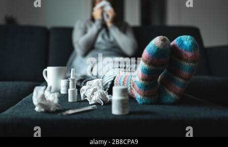 Woman sneezing and blowing nose with tissue and handkerchief. Sick and ill person with flu, cold medicine and woolen socks. Fever, virus or infection. - Stock Photo