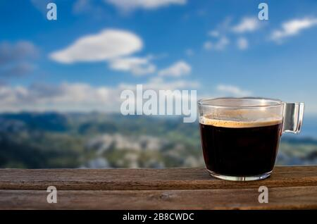 Cup of black coffee with blue sky and mountains background, Croatia. View of mountains, sky and sea in Northern Velebit National Park. Scenic mountain - Stock Photo