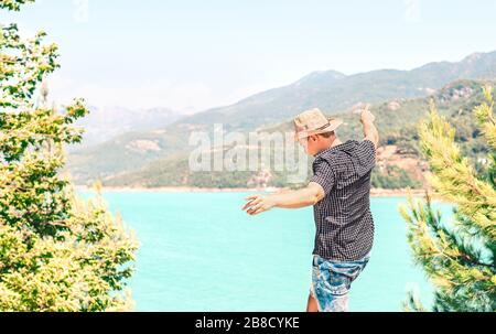 Happy man spreading arms and enjoying life in the mountain. Carefree guy with cowboy style hat feeling free. Journey to success. Freedom and fun. - Stock Photo