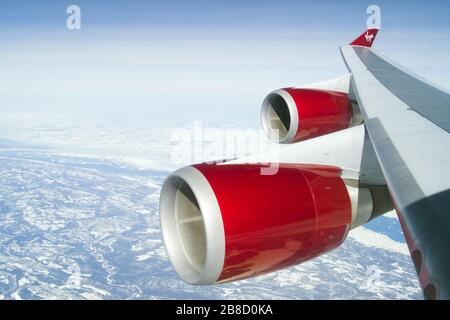 Virgin Atlantic Boeing 747-400 wing view in flight making landfall en route to New York. 747 jumbo jet quad jet quadjet four engine nacelle cowling - Stock Photo
