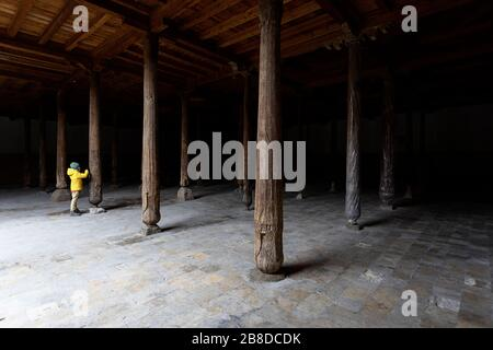 Uzbekistan, Khiva, boy in yellow jacket looking at the carved detail of the wood columns inside the old Juma mosque - Stock Photo