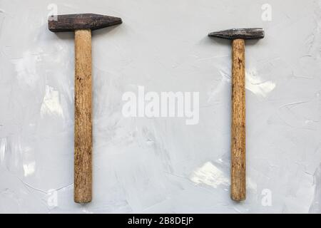 Two old rusty hammers on gray background, carpentry concept, copy space
