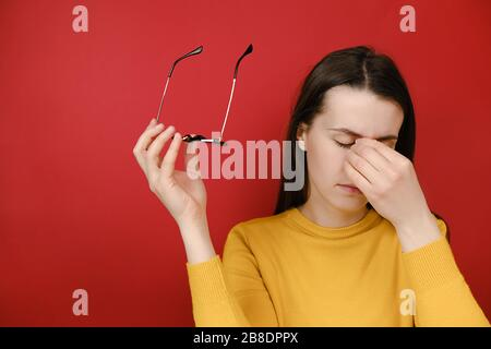 Unhappy woman taking off glasses tired massaging touching nose bridge, exhausted girl suffering from headache, feeling pain, breathing, calming down