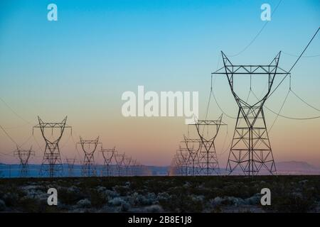USA, Nevada, Clark County, Eldorado Valley, Boulder City. The silhouette of a power transmission line vanishing into a point in the distance during su - Stock Photo