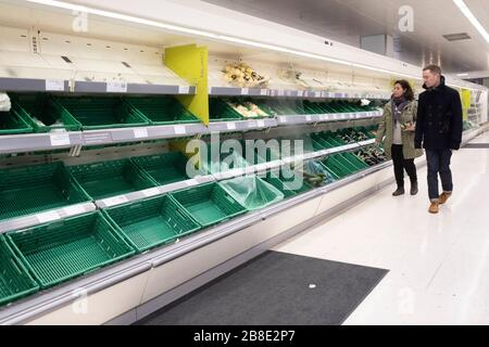 London, UK. 21st Mar, 2020. People walk by almost-empty shelves of a supermarket in London, Britain, March 21, 2020. As of 9a.m. (0900GMT) on Saturday, 72,818 people have been tested in Britain, of which 67,800 were confirmed negative and 5,018 were confirmed positive. 233 patients in the country who tested positive for the virus have died. Credit: Xinhua/Alamy Live News - Stock Photo