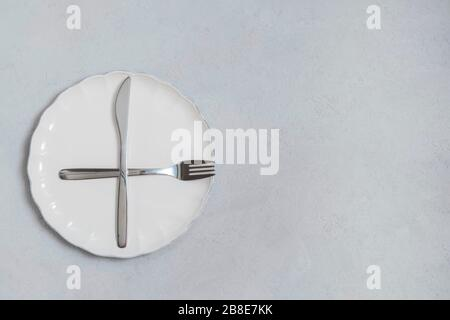 Fasting and diet concept. Empty white plate with fork and knife on neutral concrete kitchen table. Top view with copy space