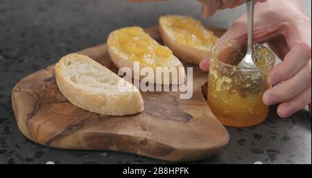 man spreading orange marmalade on ciabatta slices on wood board, wide photo - Stock Photo