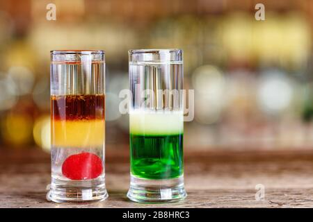 Different cocktails on the bar in a restaurant or in a pub, multilayered alcoholic drinks - Stock Photo