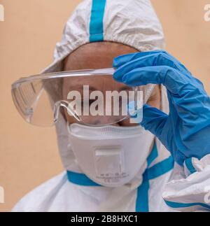 Female health worker takes off protective glasses exhausted from fatigue after battling the terrible Coronavirus Covid-19 in Italy - Stock Photo