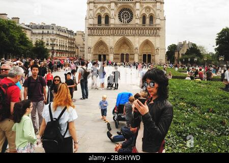 A long line of tourists waiting to enter the Cathédrale Notre-Dame de Paris and a woman checking here phone, Parvis Notre-Dame - Pl. Jean-Paul II. - Stock Photo