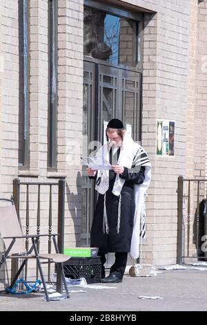 New York, United States. 21st Mar, 2020. A hasidic Satmar Jew reads a new letter outside a synagogue closed for Sabbath Prayers service due to the spread of coronavirus across the United States.The World Health Organization declared coronavirus (COVID-19) a global pandemic on March 11th. Credit: SOPA Images Limited/Alamy Live News - Stock Photo