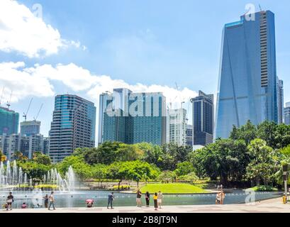 Office and residential high rise towers and fountains in Symphony Lake and tourists enjoying a day at KLCC Park Kuala Lumpur Malaysia.