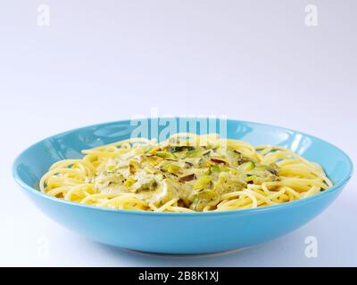 Spaghetti with a cream sauce with zucchini and leek  in a light blue plate on a white background. - Stock Photo