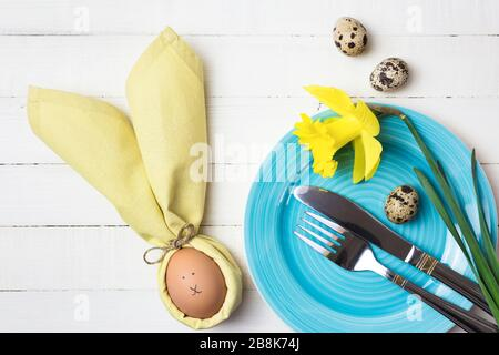 Beautiful festive Easter table setting with egg in napkin like Easter Bunny and spring flowers on white wooden table. Top view with copy space. - Stock Photo