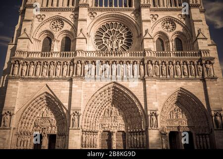 Detail of the Notre Dame Cathedral facade stone work and rose window on a sunny autumn afternoon - Stock Photo