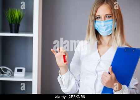 Health worker holds a test tube with a test of covid-2019 - Stock Photo