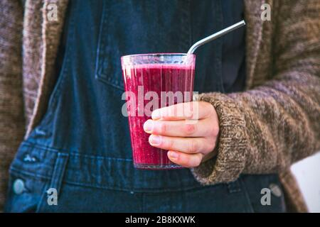 Berry vegan smoothie with chia seeds, glass of healthy smoothie in female hands, vegan alkaline diet concept, clean eating - Stock Photo