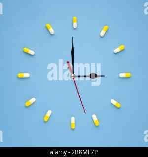 Creative healthcare and medicine concept photo of clock watch made of drugs and pills on blue background. - Stock Photo
