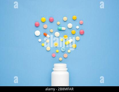 Creative healthcare and medicine concept photo of heart made of drugs and pills on blue background. - Stock Photo