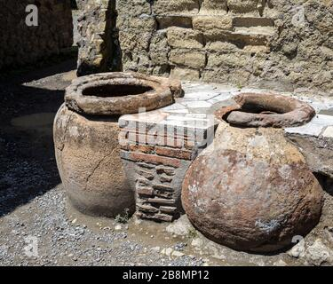 Two exposed food storage containers in the remains of a Roman food outlet, Herculaneum, Campania, Italy. - Stock Photo