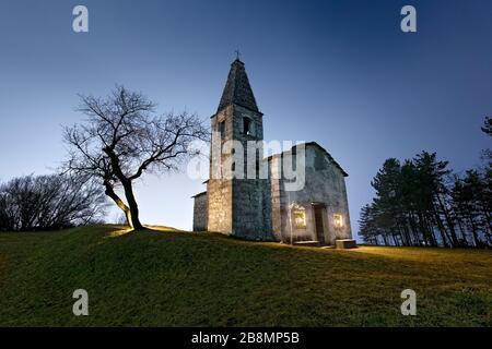 Night at the medieval church of Santa Apollonia in Manzano. Gresta Valley, Trento province, Trentino Alto-Adige, Italy, Europe. - Stock Photo
