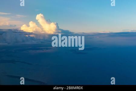 Dramatic sunset skies over Swedish coastline of Baltic Sea seen from a flying plane to Scavsta Airport just after a summer storm passing - Stock Photo