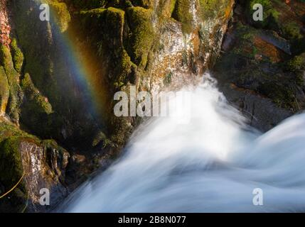 a photo taken from the top of a waterfall, revealing a rainbow down the lower arias of it. this was taken with a slow shutter speed to show the flow - Stock Photo